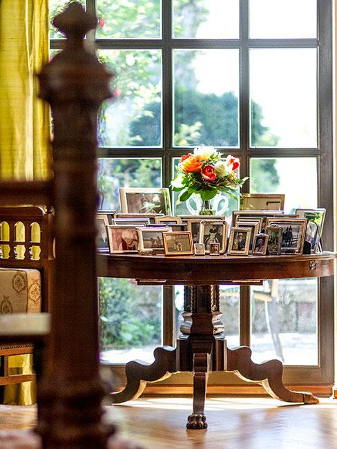 stolik pomocniczy w stylu biedermeier przy oknie z ramkami na zdjęcia
