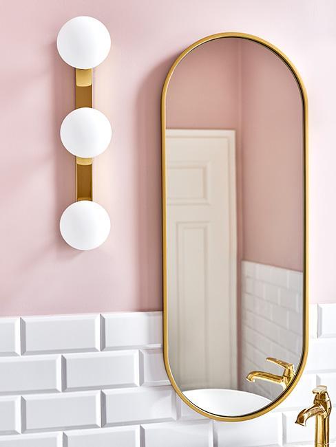łazienka z owlanym lustrem w złotej ramie i jasnoróżową ścianą