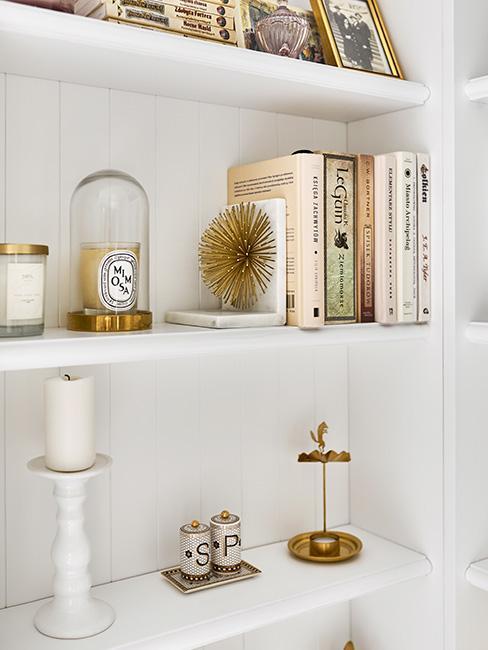 biały elegancki regał w salonie z książkami i dekoracjami w złocie