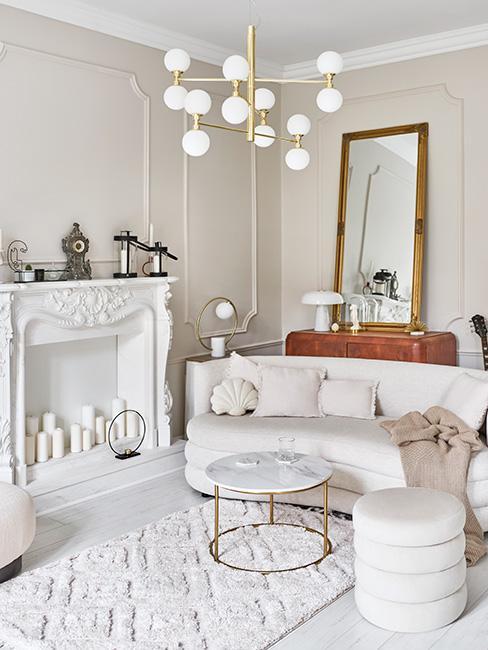 jasny salon w stylu francuskim z kominkiem, sofą nerką i sztukaterią na ścianach