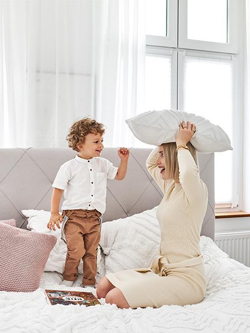 Młoda kobieta bawiąca się z synkiem na łóżku