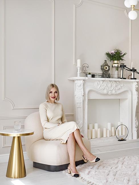 młoda kobieta w białej sukni siedząca na białym fotelu w jasnym salonie z kominkiem