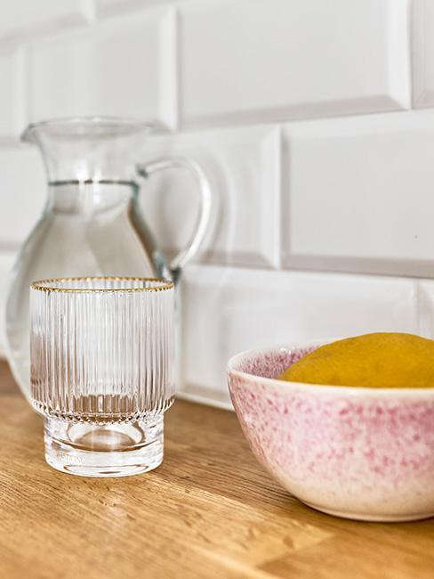różowe miski z kamionki na szafce kuchennej obok pozłacanych szklanek