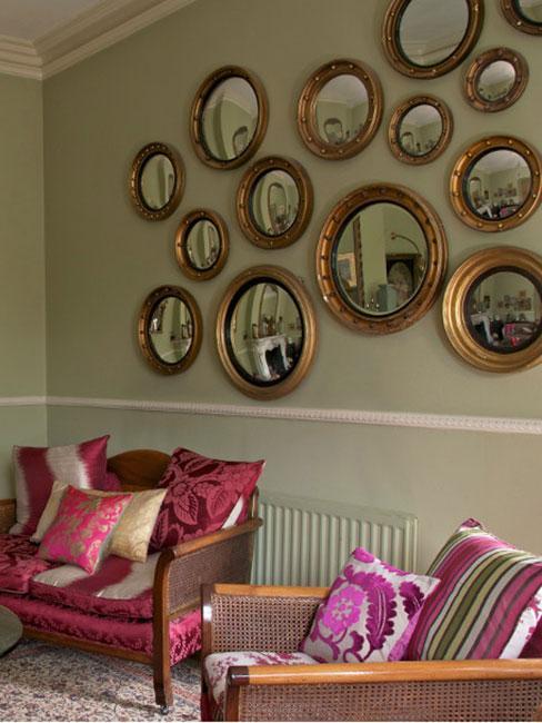 Salon w stylu wiktoriańskim z purpuroeymi fotelami tapicerowanymi z galerią wypukłych luster na ścianie