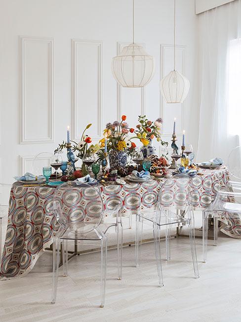 Stół zastawiony kolorową zastawą, ozdobnymi wazonami i obrusem w w kolorowe wzory