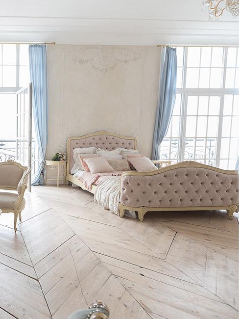 Jasna sypialnia w stylu rokoko, dobiona rama łóżka w beżowym kolorze, jasne panele na podłodze, wysokie okna i błekitne zasłony