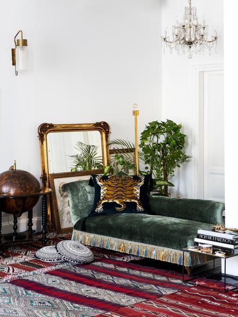 Salon, z sofą w kolorze butelkowej zieleni , lustrem w złotej ramie, roslinami, poduszkami dekoracyjnymi w zwierzęcy wzór i kilkoma kolorowymi dywanami na podłodze