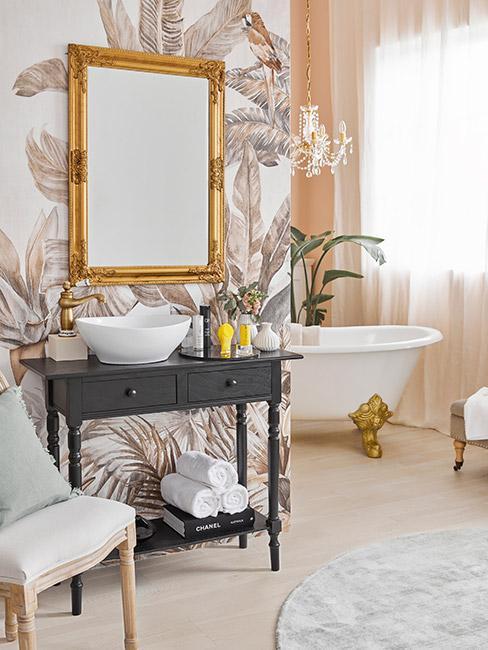 łazienka w stylu rokoko, Tapeta na ścianie w jasne liście, złote lustro, szafka pod umywalkę w kolorze ciemnoszarym, biała wanna na złotych nóżkach