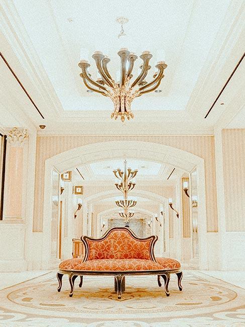 Jasne pomieszczenie z lustrem na całej ścianie, jasnymi ścianami i okrągłą wzorzystą pomarańczową sofą