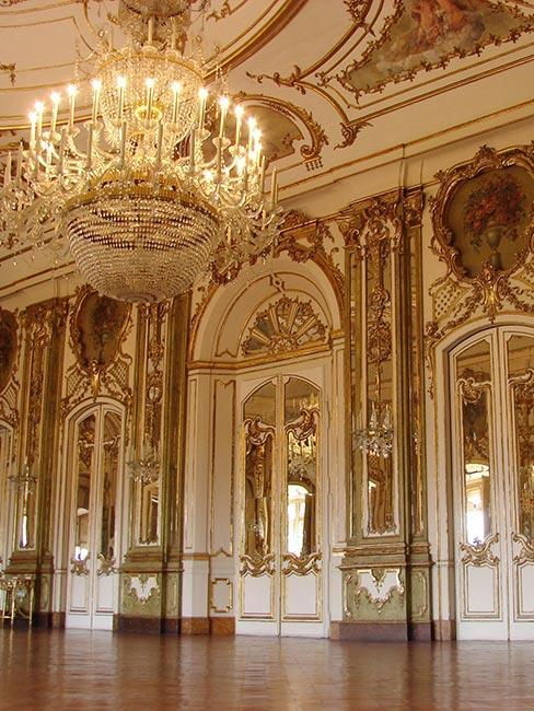 Bogato zdobione wnętrze, ze złotymi dekoracjami na ścianach, ozdobne okna i drzwi, na zdobionym suficie zyrandol
