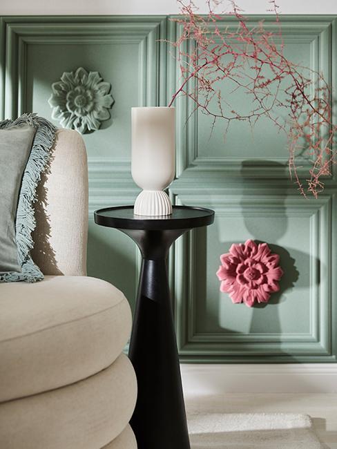 Biały fotel z dekoracyjną poduszką w kolorze zielonym, takim samym jak ściana ze sztukaterią, obok mały stolik z ciemnego drewna, na nim biały wazon