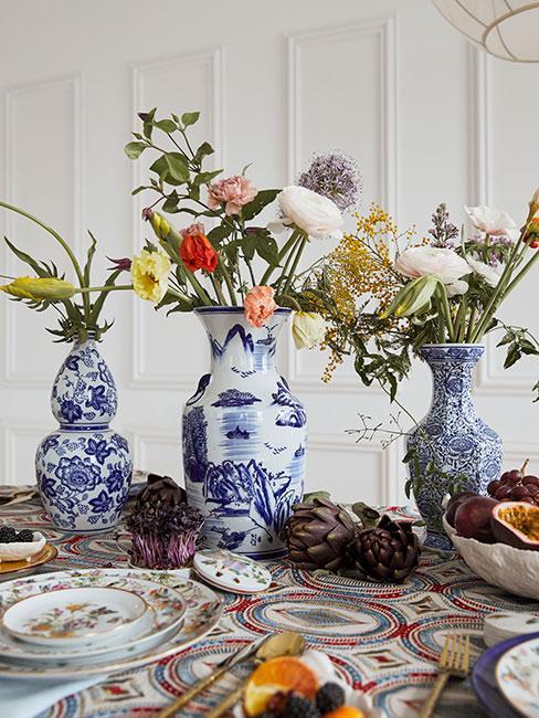 Biało niebieskie zdobione wazony z kwiatami na stole