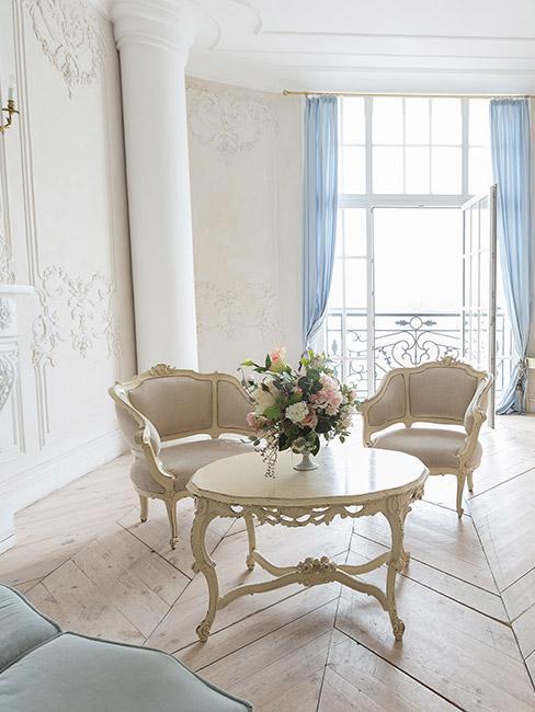 Przestronny salon, z jasnymi meblami w stylu rokoko, bukietem kwiatów na stoliku, wysokomi oknami i jasnymi ścianami