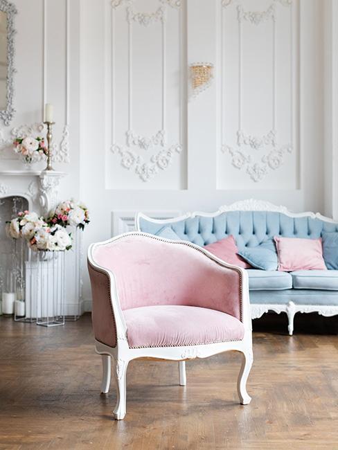 Jasna przestrzeń z białymi ścianami, drewnianą podłogą, różowym fotelem i błękitną sofą