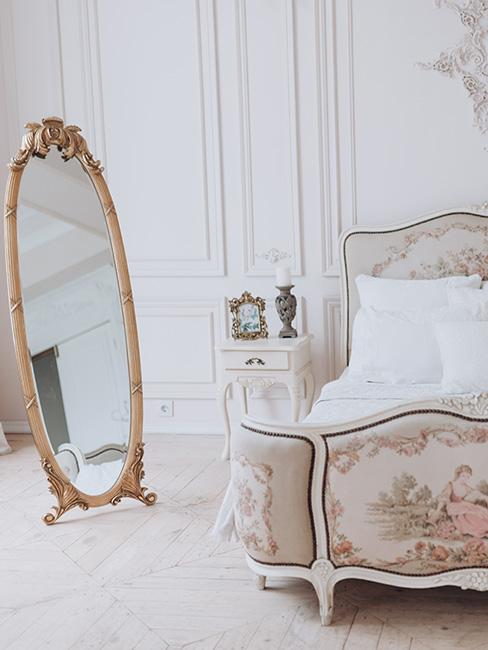 Bogato zdobione lóżko z malunkami z przodu i na wezgłowiu, biała pościel, biały stolik nocny ze świecznikiem obok stojące lustro w złotej ramie