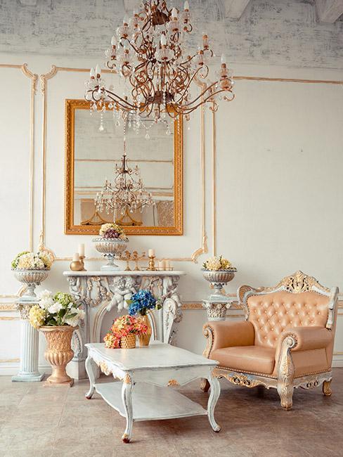 Salon w stylu rokoko, fotel w łososiowym kolorze z białym rantem, biały ozdobny stolik, żyrandol na suicie, na jasnej ścianie duże lustro w złotej ramie