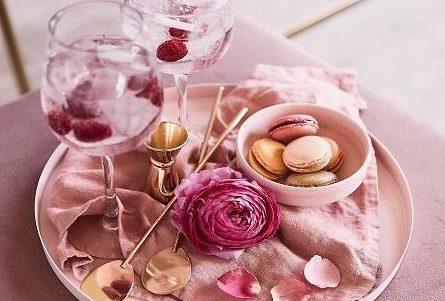 Różowa zastawa stołowa, taca do serwowania, na niej rózowa miseczka i kieliszki z płatkami róż w środku, wszystko to na małym różowym stoliku s