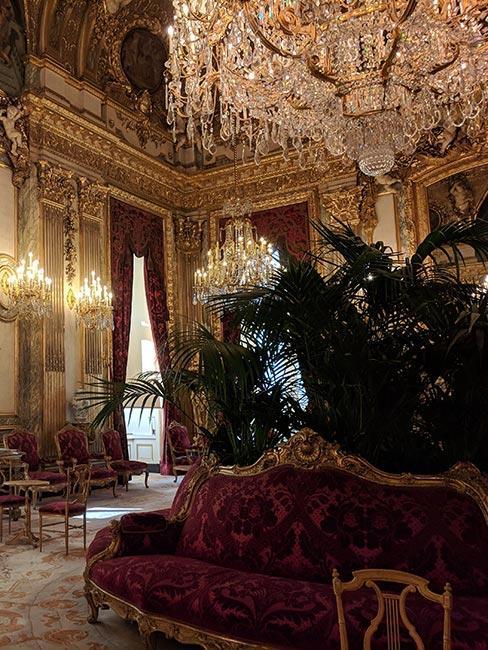 Bogato zdobione pomieszczenie, ze złotymi kinkietami na ścianie, ozdobionymi kryształami, żyrandol na suficie cały w kryształach, wysokie sufity, dekoracje na ścianach w kolorze złota, burgundowe zasłony, burgundowe meble ze złotym rantem i ozdobne duże rośliny