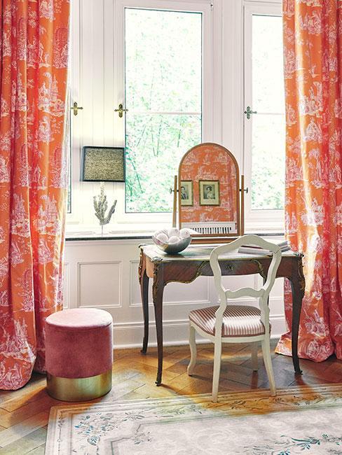 mała drewniana toaletka z białym krzesłem, duże okno z wzorzystymi zasłonami, obok mały puf w różowym kolorze