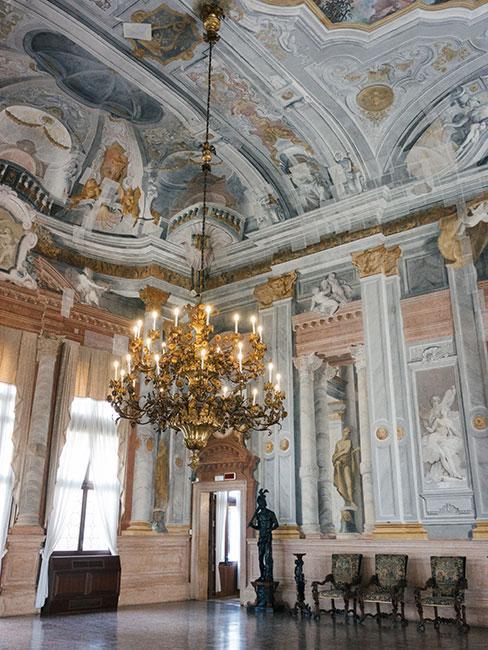 wnętrze w stylu rokoko, ściany bogato zdobione malunkami w kolorze białym, niebieskim i różowym, na suficie żyrandol