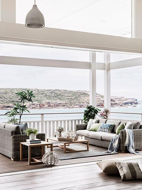 taras nad morzem z szarymi sofami i błękitnymi poduszkami w stylu hampton