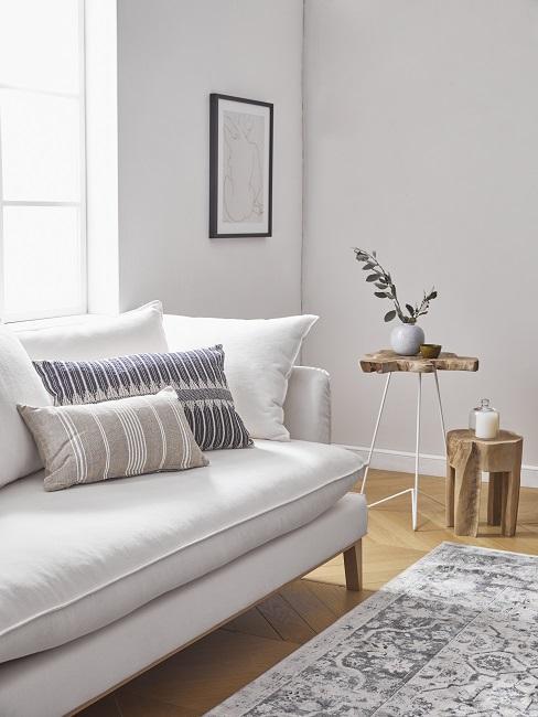 biała tapicerowana sofa z poduszkami w delikatne pasy obok drewnianego stolika