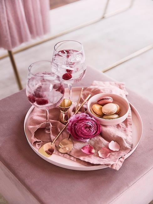 makaroniki i róże na dekoracyjnej tacy obok kieliszków z różowym koktajlem