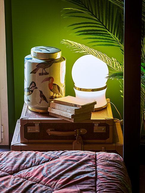 wazon oobok lampki nocnej na skórzamyn kuferku na tle zielonej ściany