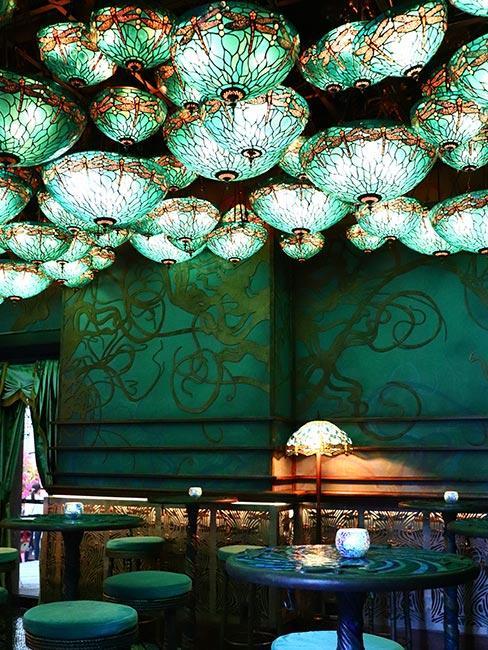 ciemnozielone wnętrze kawiarni z licznami lampami w kształcie meduz na suficie w stylu art nouveau