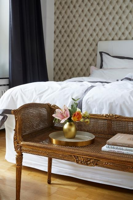 drewniana ławka przy łóżku w stylu secesyjnym