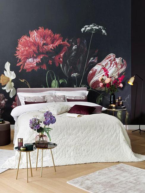Sypialnia z ciemną fototapetą na ścianie za łóżkiem w duże holenderskie kwiaty