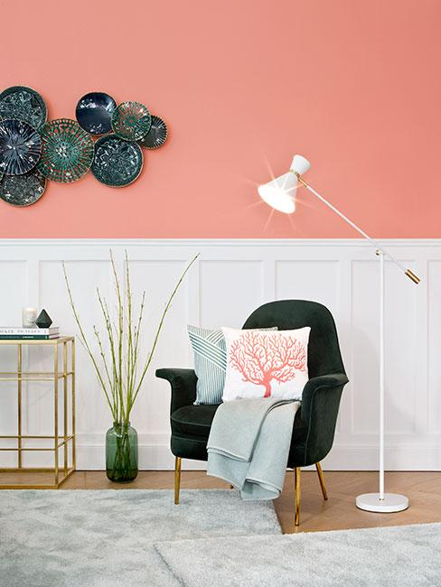 zielony fotel na tle ściany z lamperią w łososiowym salonie