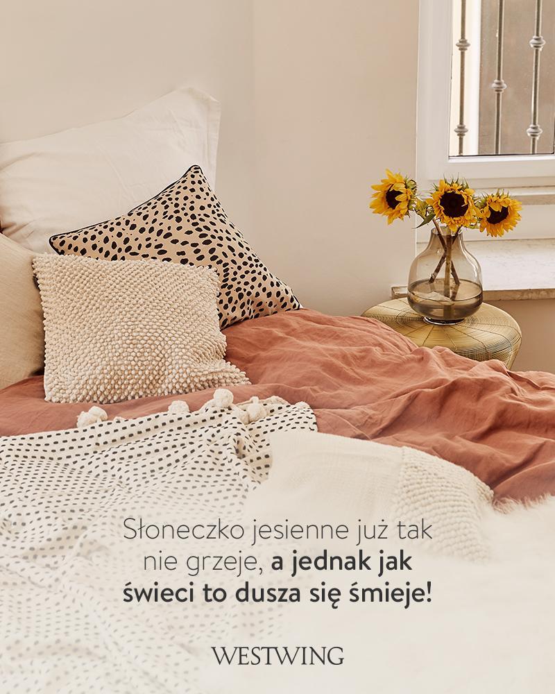 przytulna sypiaqlnia z łososiową pościelą i poduszką w panterkę
