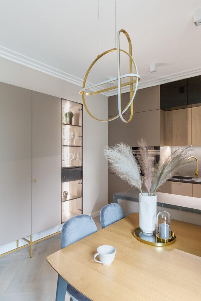 Jadalnia z drewnianym stołem a nad nim dekoracyjną, złotą lampą