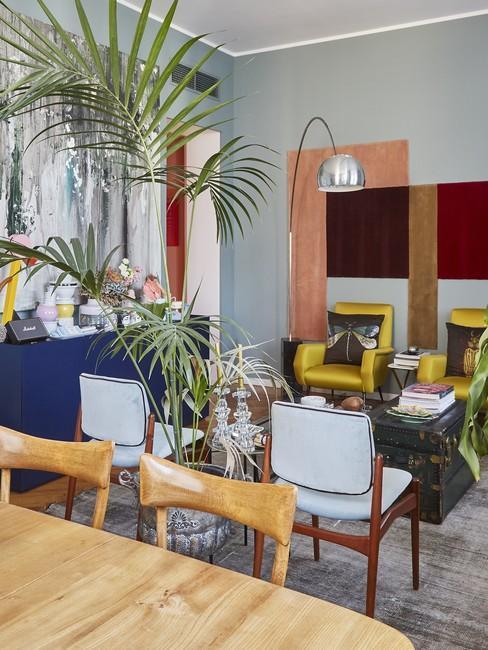 jadalnia w salonie ekscentrycznym, kolorowe kształty na ścianie, fotele w żółtym kolorze, duża palma na środku pokoju