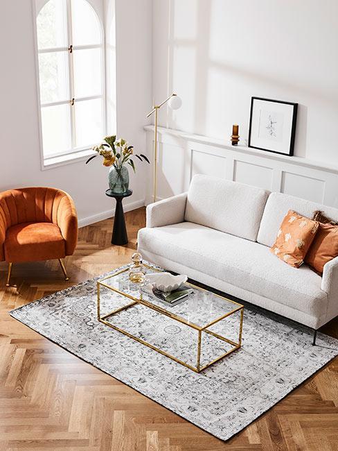 Przestronny salon w stylu mid century modern, drewniana podłoga biała sofa, fotel w kolorze terakota, mały złoty stolik ze szklanym blatem