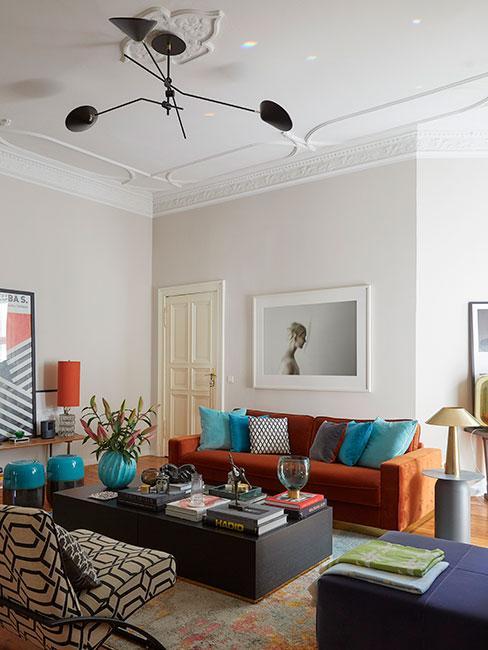 Przestronny salon, kanapa w kolorze terakota z turkusowymi poduszkami, ciemny stolik kawowy, białe ściany, wysokie białe sufity