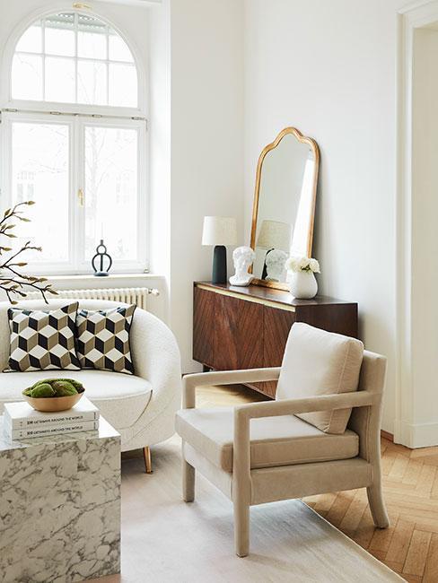 drewniana toaletka z dużym lustrem, biała sofa, jasny fotel, marmurowy stolik kawowy, drewniana podłoga