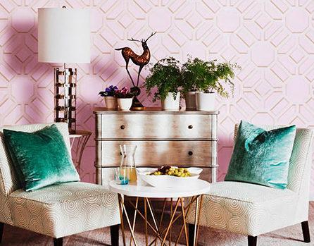 Kącik z dwoma fotelami, małą komodą w białym kolorze białą podłogową lampką na tle różowej ściany