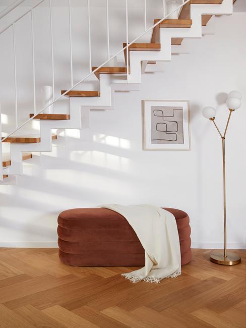 przestrzeń obok schodów urządzona minimalistycznie, mały brązowy puf , biały kocyk, złota podłogowa lampa