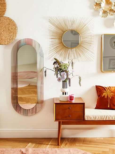 Przedpokój w stylu mid century modern, lustro w złotej ramie na ścianie, obok drugie ;ustro z kolorowej ramie, szafka z siedziskiem w miodowym kolorze