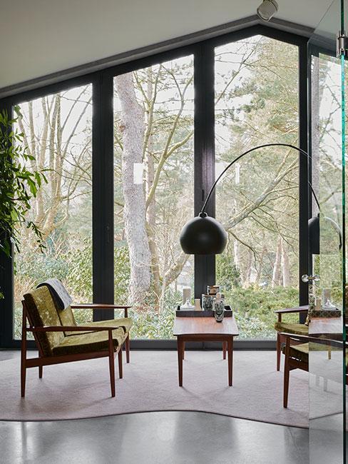 Salon w stylu loftowym, ciekawe fotele w zielonym odcieniu, mały stolik kawowy, cała ściana przeszklona
