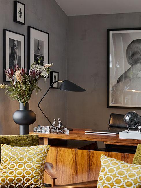 Gabinet w stylu mid century modern, drewniane biurko, czarna lampka, szare ściany na których wiszą obrazy w czarnej ramie