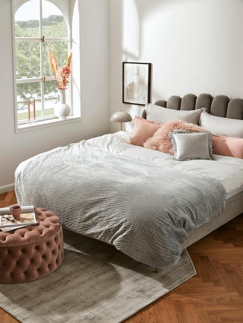 Sypialnia w stylu mid century modern, szare wezgłowie łóżka, szara narzuta, różowe dodatki, różowy puf