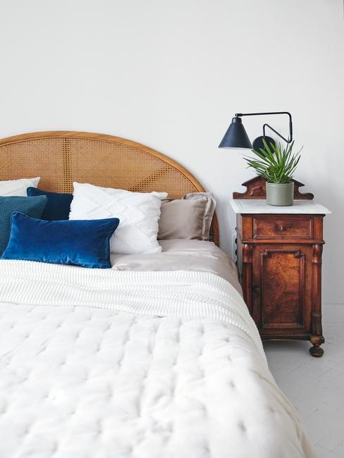 Łózko z białą narzutą, granatowymi poduszkami, drewnianym wezgłowiem, obok szafka nocna ciemnego drewna