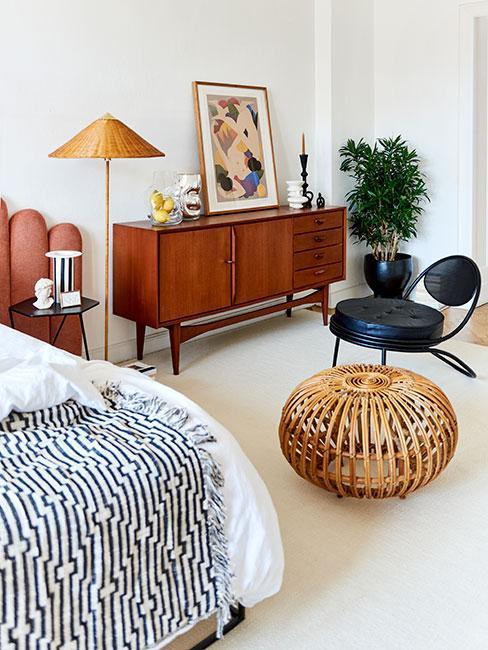 Sypialnia w stylu mid century modern, komoda z ciemnego drewna, czarny fotel, stolik kawowy z wikliny, obok łózka różowy fotel, łóżko przykryte białą narzutą i czarno białym kocem