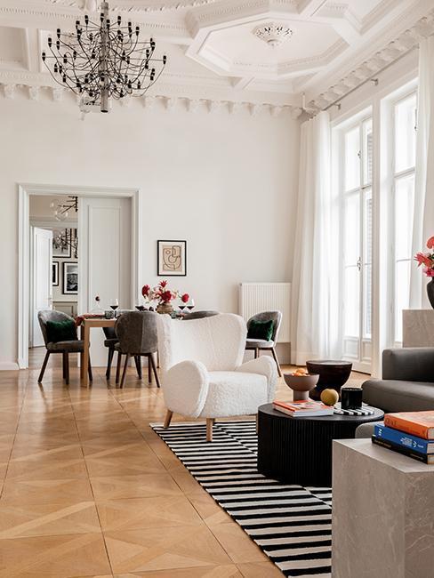 Salon w stylu mid century moder, otwarta przestrzeń, drewniana podłoga, czarno biały dywan, kolorowe dodatki