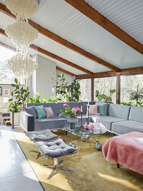 salon w lofcie z szarą sofą i pastelowymi tekstyliami i srebrnym stolikiem kawowym w stylu mid century modern