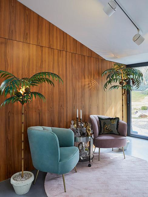 dwa pastelowe fotele z weluru na tle ściany z boazerii w lofcie w stylu mid century modern