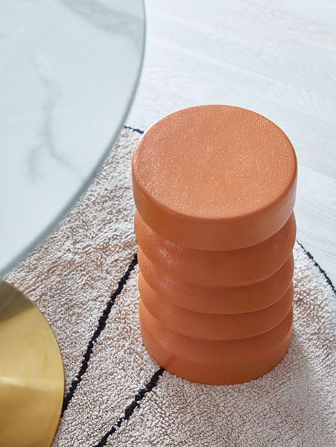 Pomarańczowy puf na dywanie obok stołu